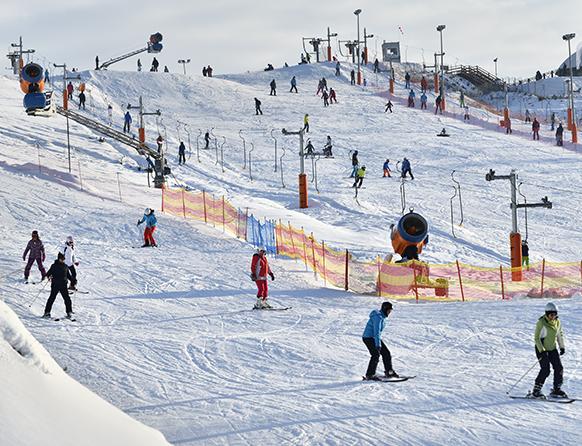 Zdjęcie przedstawia ośnieżoną Kurzą Górę a dokładnie stok narciarski zimą, podczas jazdy miłośników sportów zimowych.