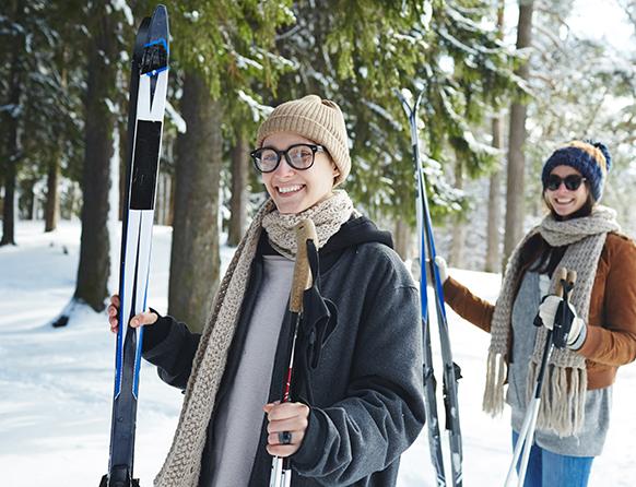 Dwie młode uśmiechnięte dziewczyny trzymające narty biegowe i kijki, będące zimą w zasypanym śniegiem lesie.