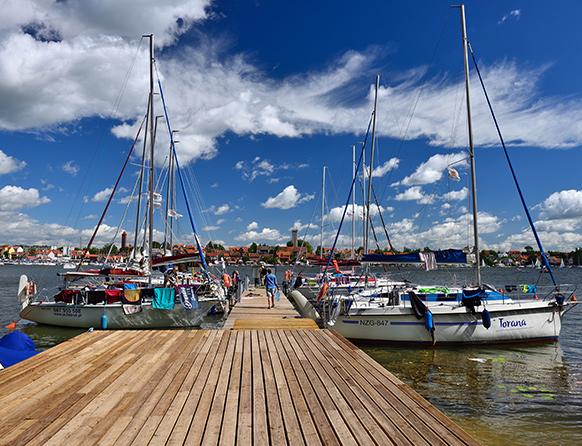 Zdjęcie przedstawia mrągowską przystań żeglarską, gdzie przy drewnianym pomoście zacumowane są liczne łodzie.