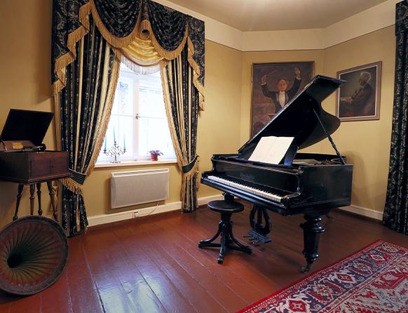 Pokój w muzeum salonu muzycznego im. Feliksa Nowowiejskiego w Barczewie, a w nim zabytkowe pianino i adapter.