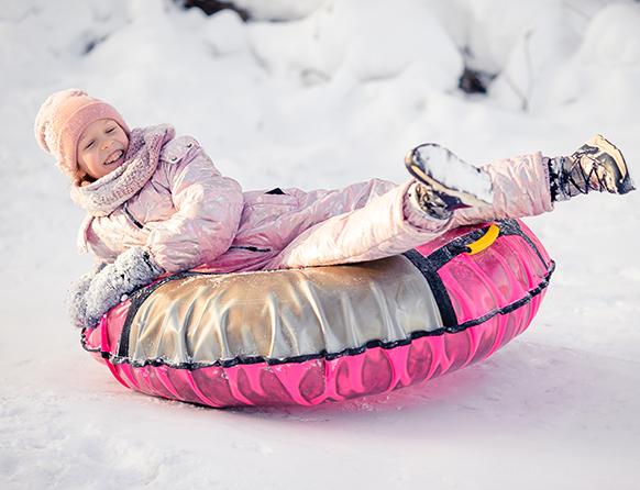 Zadowolona dziewczynka zjeżdżająca zimą na śniegu na tzw. dmuchanej kolorowej oponie.