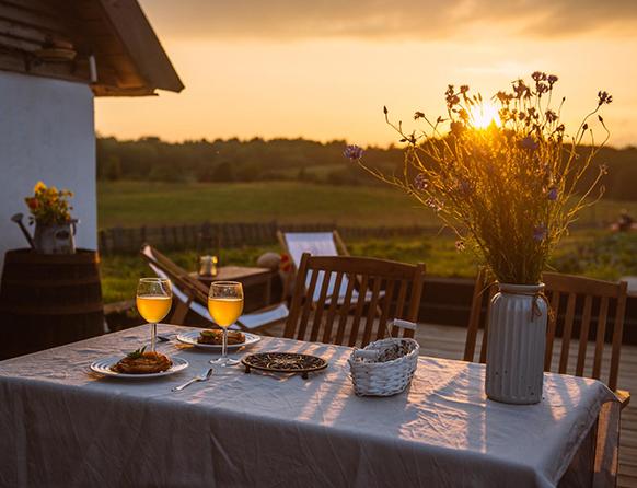 Zdjęcie ukazuje stół ustawiony na świeżym powietrzu, na którym ustawiona jest kolacje i kieliszki napełnione jasnym trunkiem.  Dookoła rozprzestrzeniają się zielone pola, a przez kwiaty ustawione w wazonie na stole przedziera się zachodzące pomarańczowe słońce.