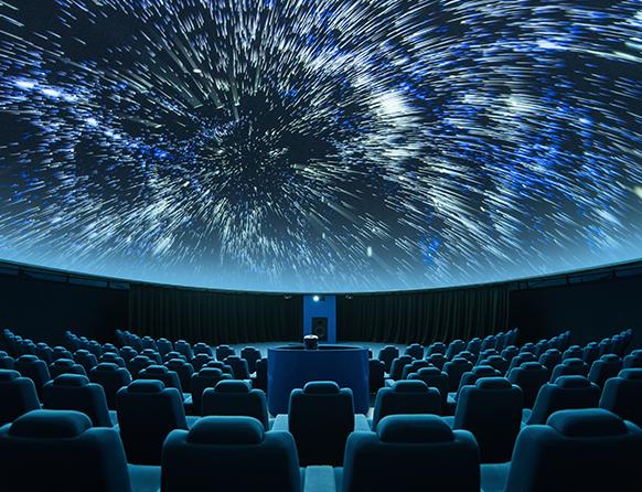 Zdjęcie przedstawia Planetarium w Olsztynie podczas wyświetlania pokazu. Prezentowany na sklepieniu planetarium obraz gwiazd daje niebieską poświatę na pusto stojące fotele.