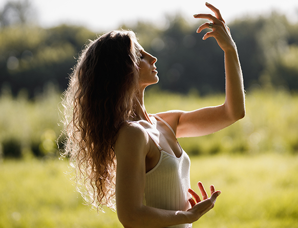 Zdjęcie pokazuje młodą brunetkę z długimi włosami, ustawioną z wysoko uniesioną głową oraz rękoma wskazującymi na moment tańca - jedna ręka uniesiona jest ku górze, druga ku dołowi. Kobieta ubrana jest w białą sukienkę na cienkich ramiączkach.