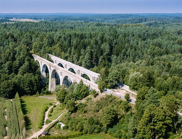 Zdjęcie przedstawia widok z lotu ptaka wysokich wiaduktów w Stańczykach wystających ponad wysokość okolicznych lasów.