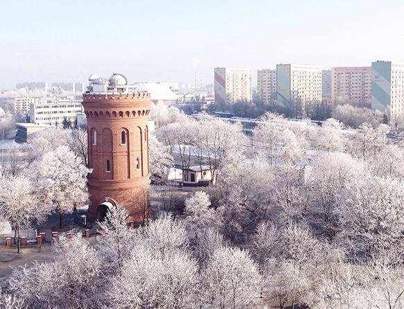 Zdjęcie przedstawia obserwatorium astronomiczne w Olsztynie, wyłaniające się spośród oszronionych drzew. Obserwatorium Astronomiczne w Olsztynie znajduje się w zaadaptowanej wieży ciśnień, zbudowanej w 1897 na wzgórzu Świętego Andrzeja.