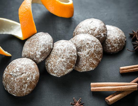 Na zdjęciu sześć ciastek koloru brązowego podobnych do pierników zwanych brukowcami.  Swoją nazwę zawdzięczają temu, że na jego wierzchnią warstwę składają się małe, ściśle przylegające do siebie kulki przypominające bruk. Obok ciastek znajduje się obrana skórka pomarańczy oraz trzy laski cynamonu.
