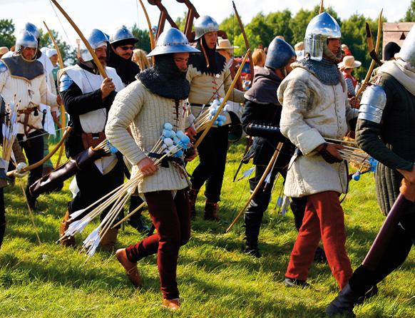 Inscenizacja bitwy po Grunwaldem. Maszerujący rycerze-statyści ubrani w hełmy i kolczugi oraz w średniowieczne stroje niektóre koloru białego. Każdy z rycerzy posiada białą broń w tym łuki i strzały.