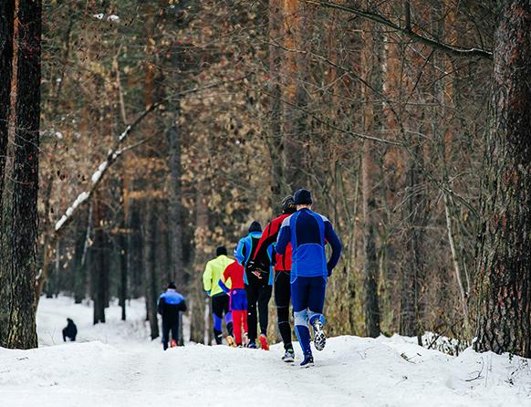 Zawodnicy biegnący gęsiego zimą po śnieżnej ścieżce leśnej.
