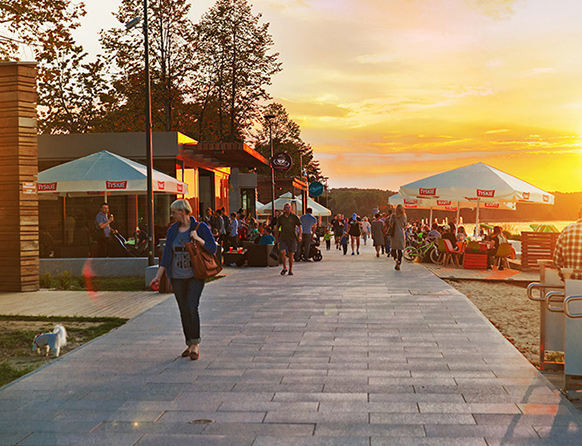 Zdjęcie przedstawia wieczór na plaży miejskiej w Olsztynie. W ogródkach restauracyjnych pod parasolami siedzą ludzie, a inni spacerują z psami.