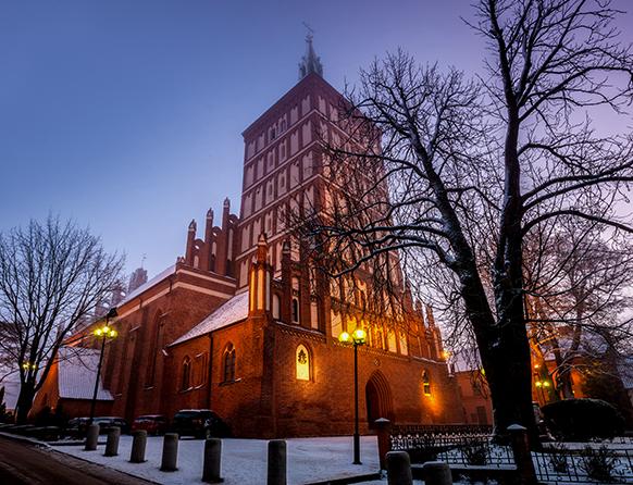 Zdjęcie przedstawia katedrę w Olsztynie w porze zimowej. Wieczorowa pora sprawia, że wokół świątyni zapalone są latarnie.