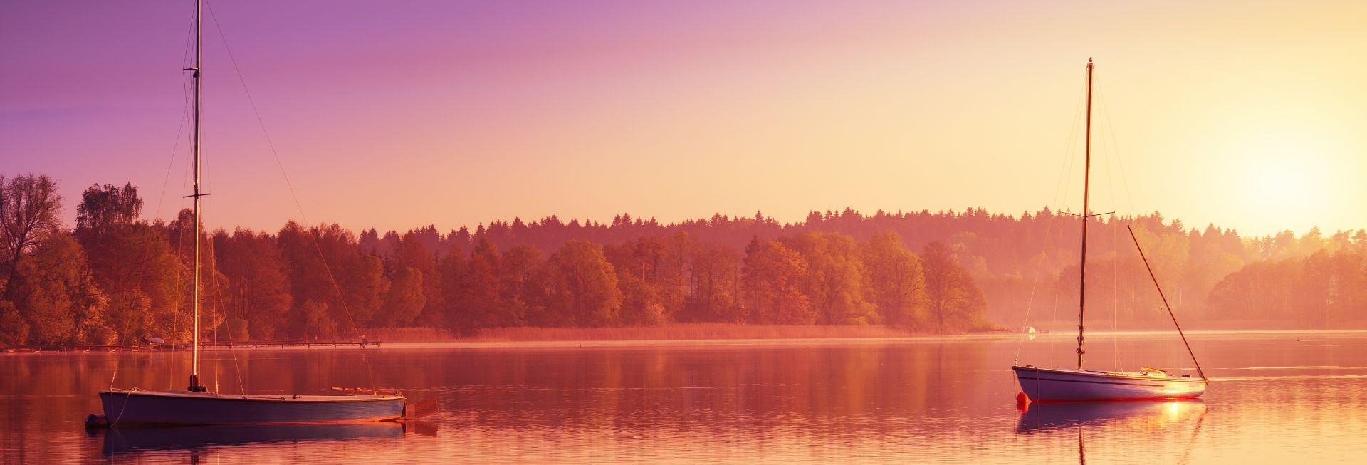 Zdjęcie przedstawia dwie łódki bez załogi dryfujące na jeziorze w czasie zachodu słońca chowającego się za linią drzew.