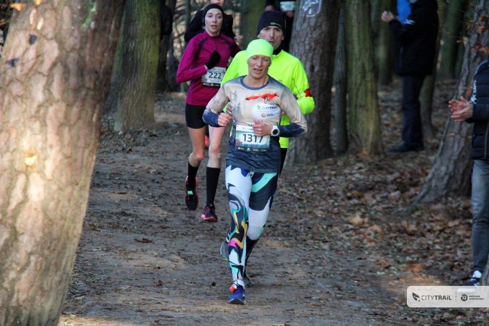Zdjęcie przedstawia biegaczy podczas zawodów na leśnej ścieżce.