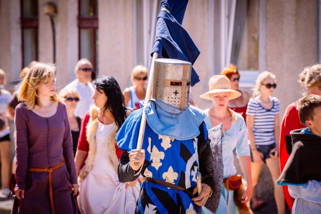 Parada rycerska ulicami Rynu. Na pierwszym planie maszerujący rycerz trzymający flagę, ubrany w średniowieczny strój niebieskiego koloru i hełm. Za nim w paradzie idą kobiety, ubrane niektóre w stroje z epoki średniowiecza.