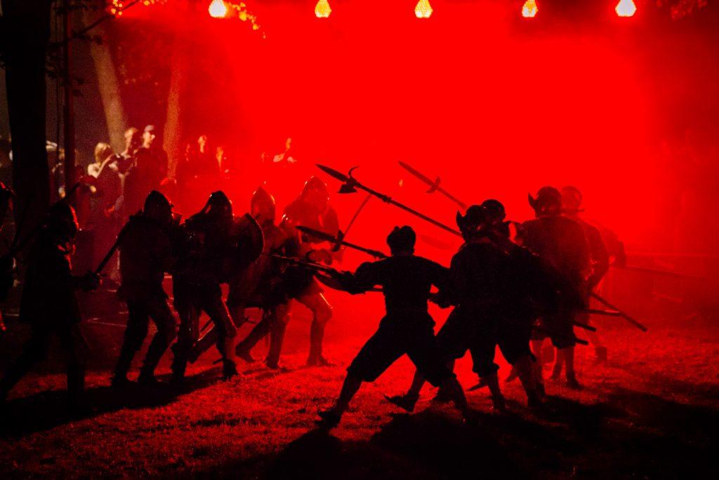 Inscenizacja walk rycerskich podczas obrony Zamku w Rynie. Na pierwszym planie dwie grupy po siedmiu rycerzy stojących na przeciw siebie i wymachujących mieczami i długimi włóczniami. Tłem bitwy są czerwone światła oraz sztuczny dym.
