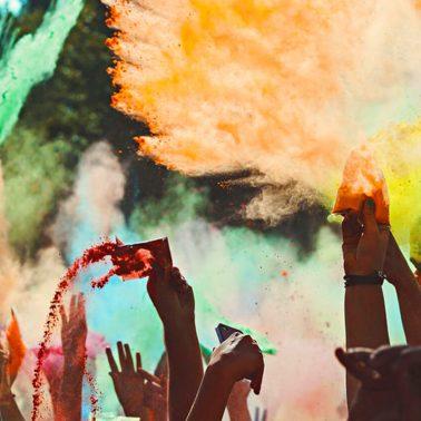 Zdjęcie przedstawia ręce tańczących uczestników festiwalu, którzy posiadając kolorowe woreczki z proszkiem, wysypują na tańczących uczestników koncertu.