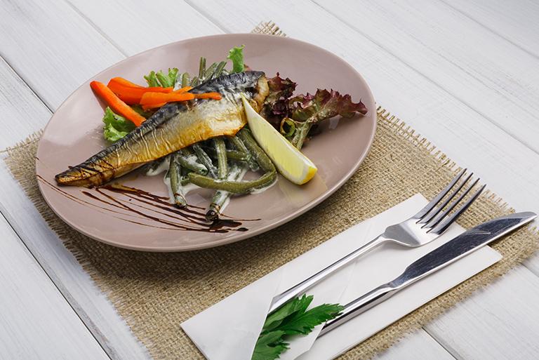 Zdjęcie ukazuje podany posiłek z restauracji Młyński Staw. Na jasnobrązowej podstawce położone są sztućce oraz talerz na którym ułożona jest sałata, a na niej kawałek wędzonej ryby przybrany dekoracyjnie czerwoną marchewką oraz cząstką cytryny.