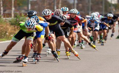 Zdjęcie przedstawia zawodników - rolkarzy ścigających się i rywalizujących na drodze asfaltowej.