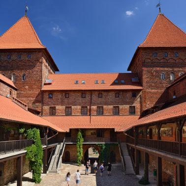 Zdjęcie przedstawia dziedziniec murowanego zamku z potężnymi wieżami.