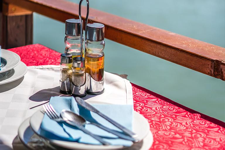 Zdjęcie przedstawia fragment nakrytego stołu w Restauracji na wodzie. Na małych białych talerzach ułożone są niebieskie serwetki oraz srebrne sztućce, a na środku stoją butelki z przyprawami, oliwą i octem.  Za stołem widnieje drewniana balustrada za którą pojawia się niebieski kolor wody.