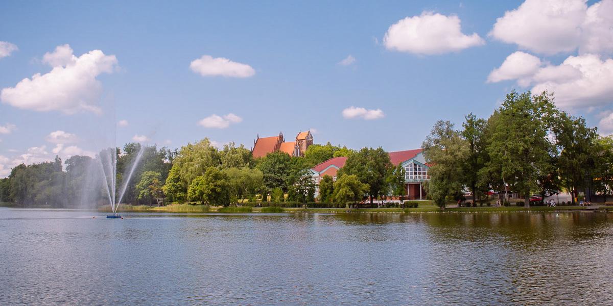 Jezioro Mały Jeziorak z fontanną na wodzie w centrum miasta Iławy. W tle panorama promenady miejskiej.