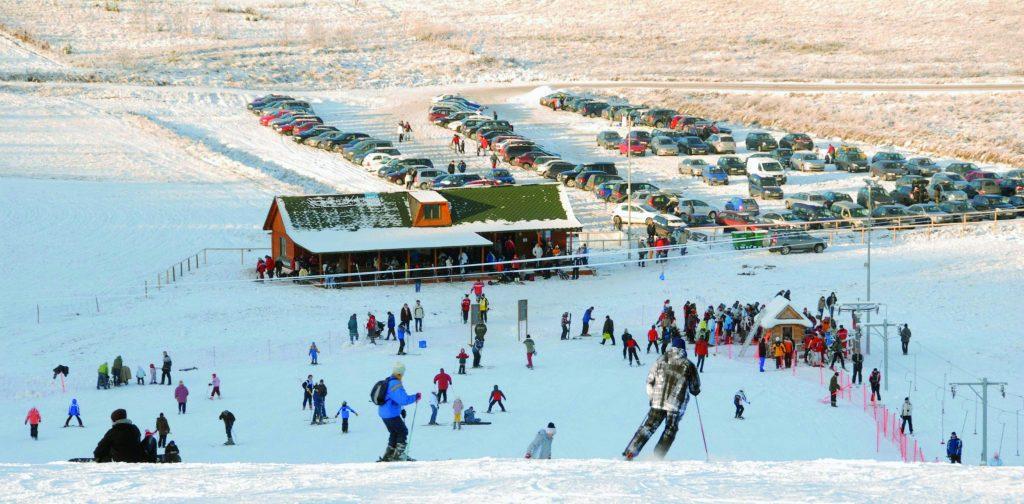 Zdjęcie przedstawiające zimę na stoku narciarskim w Rusi. Wszystko pokryte jest białym śniegiem, a na górze szaleją miłośnicy zimowych sportów takich jak jazda na nartach. W oddali widać pełen parking samochodowy.