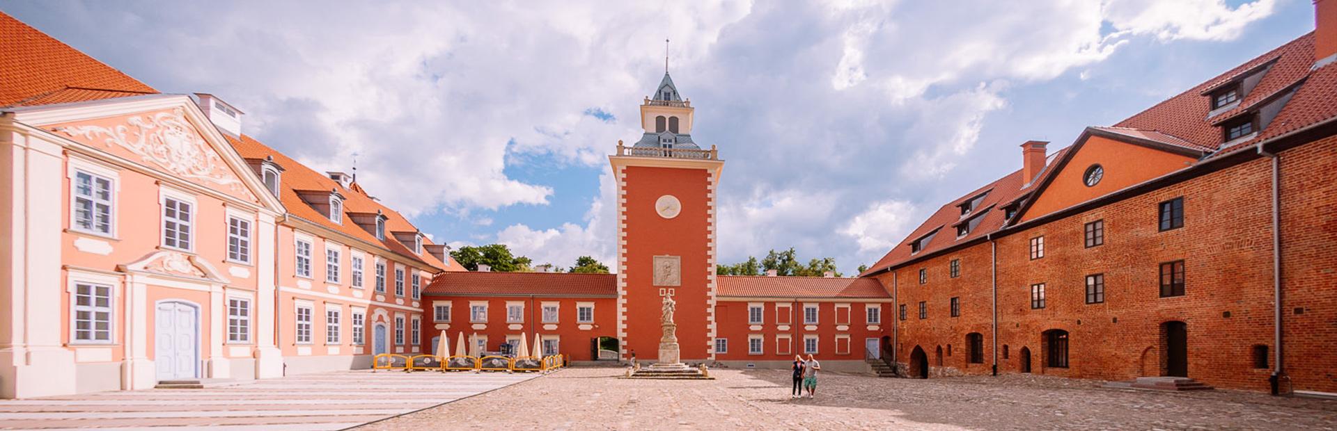 Dziedziniec zamkowy hotelu Krasicki w Lidzbarku Warmińskim. Po prawej i lewej stronie zabytkowe budynki hotelu Krasicki. Dziedziniec zamkowy wyłożony kamieniem, po środku dziedzińca rzeźba a w centralnej części zdjęcia znajduje się zabytkowa wieża z przylegającym budynkiem.