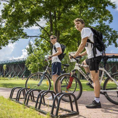 Zdjęcie przedstawia dwóch rowerzystów stojących przy stojaku rowerowym nieopodal tężni solankowej w Gołdapii.