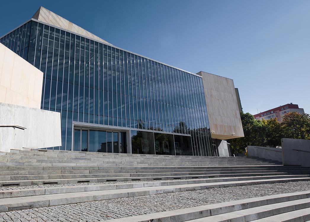 Zdjęcie przedstawia szklaną wysoką elewację wejściową filharmonii w Olsztynie, do której prowadzą kamienne schody.