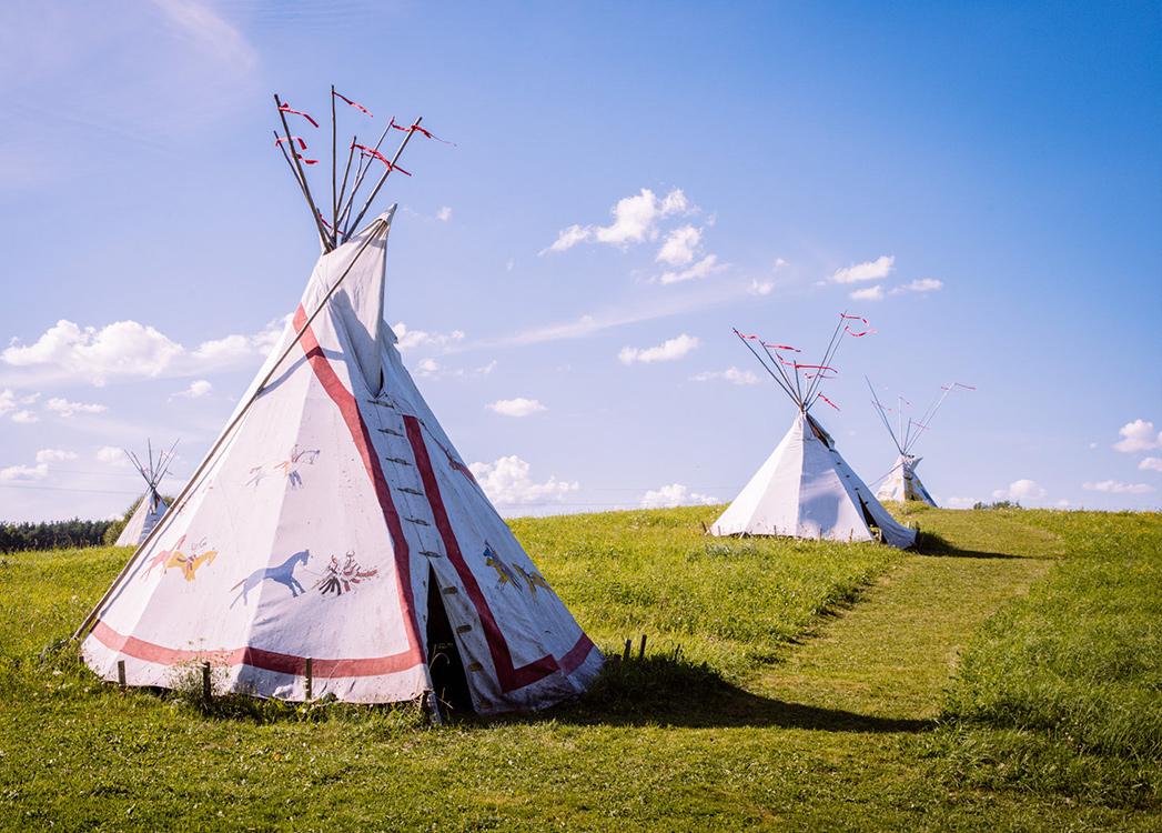 Zdjęcie przedstawia Indiańską Wioskę w Spytkowie składającą się z indiańskich białych namiotów ustawionych na zielonej trawie.