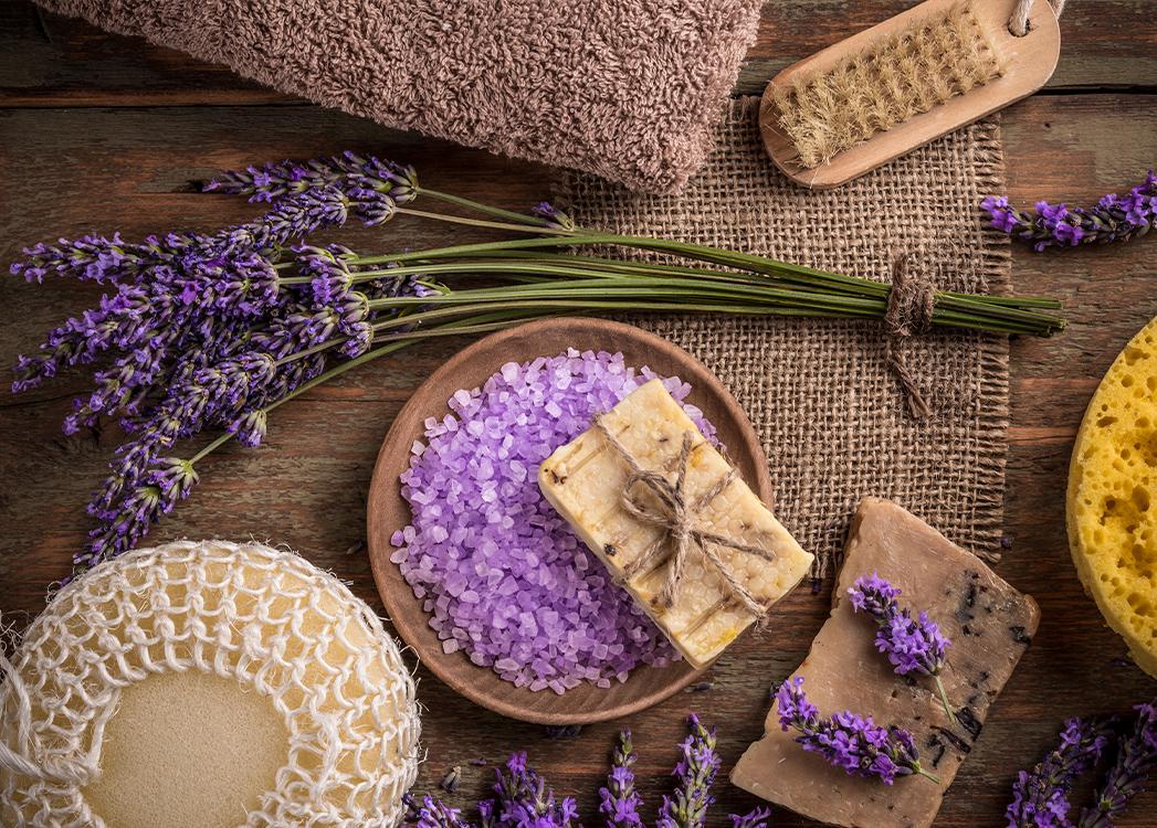 Na zdjęciu ukazany jest pęczek ściętej fioletowej lawendy, a dookoła niej leży mydło zawinięte w naturalny sznurek, jak również granulki do kąpieli o lawendowym kolorze oraz akcesoria do mycia takie jak gąbki, szczotka i ręcznik. Wszystko jest w lawendowym bądź brązowym kolorze.