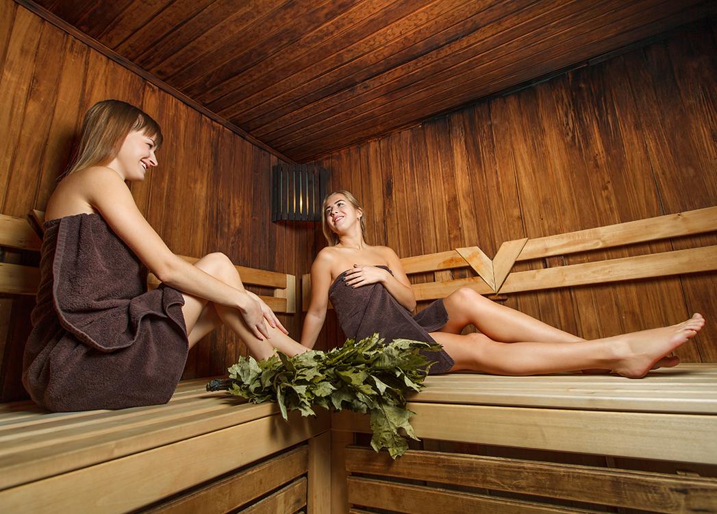 Zdjęcie przedstawia owinięte brązowymi ręcznikami dwie kobiety siedzące w drewnianej saunie.