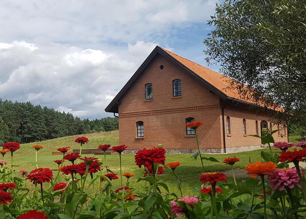Zdjęcie ukazuje gospodarstwo agroturystyczne w Wipsowie. Budynek wykonany z jasnoczerwonej cegły ma dwie kondygnacje, a zakończony jest spadzistym dachem w kolorze zbliżonym do elewacji. Przed gospodarstwem kwitną kwiaty, a w oddali widać iglasty las.