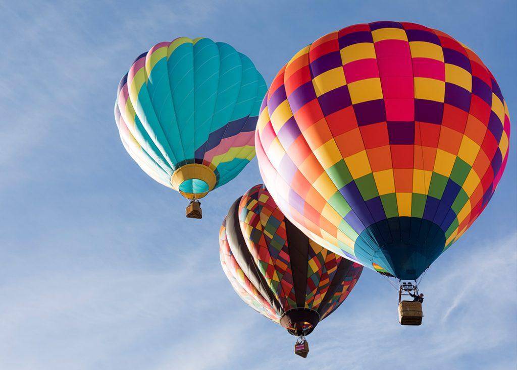 Zdjęcie przedstawia latające po niebie różnokolorowe balony z wiklinowymi koszami w których ludzie podziwiają ziemię z góry.