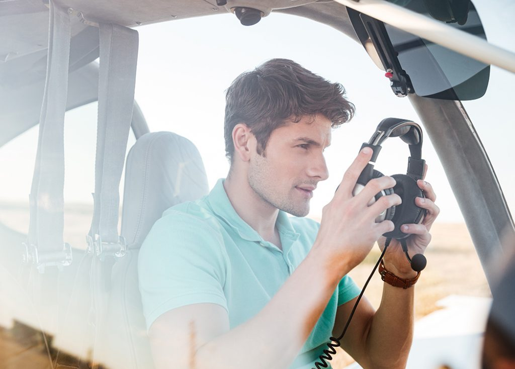 Zdjęcie przedstawia młodego pilota w turkusowej koszulce przygotowującego się do startu maszyny.
