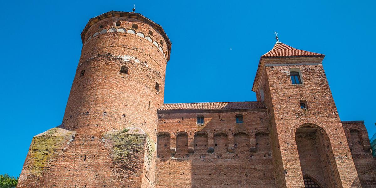 Zdjęcie przedstawia zbliżenie dwóch wież zamku w Reszlu z czego jedna jest wyższa a druga niższa. Pomiędzy wieżami biegnie mur ze zdobieniami oknami.