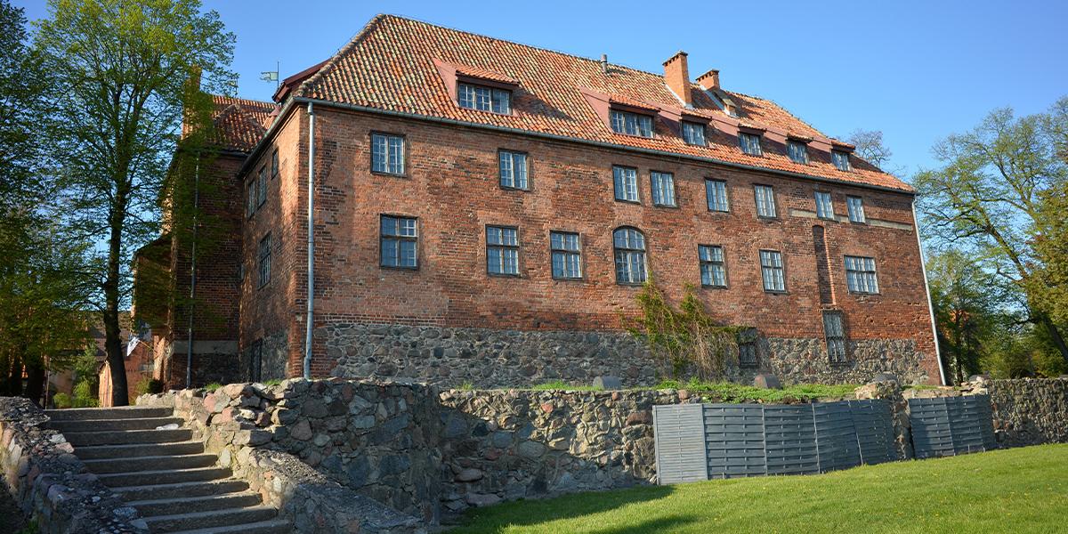 Na zdjęciu znajduje się boczna krawędź zamku w Kętrzynie. Murowana brunatna elewacja ma liczne drewniane okna różnych wymiarów. Z placu prze zamkiem biegną kamienne schody do poziomu z soczystą równo przyciętą trawą.