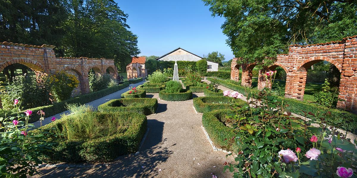 Park w Pałacu Nakomiady, z pięknie przyciętym nisko żywopłotem posadzonym pomiędzy ścieżkami. W środku okręgów z żywopłotu posadzone kwiaty.