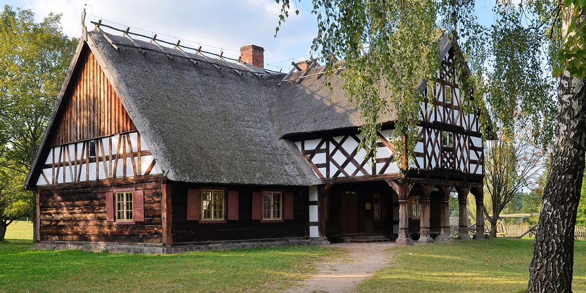Zdjęcie przedstawia drewnianą chatę z dachem pokrytym strzechą. Okna mają drewniane okiennice, a na elewacji widnieje częściowo tak zwany mur pruski czyli rodzaj ściany szkieletowej.