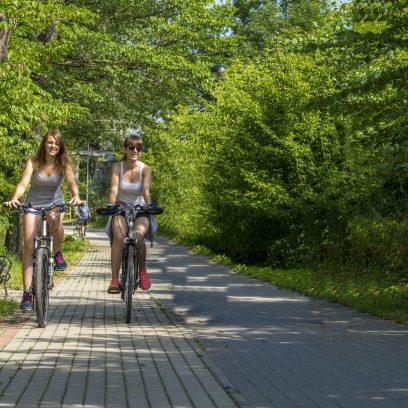 Zdjęcie przedstawia dwie rowerzystki jadące ścieżką rowerową wykonaną z kostki brukowej. Ścieżki biegnie od ulicy Armii Krajowej do ul. Zamkowej.