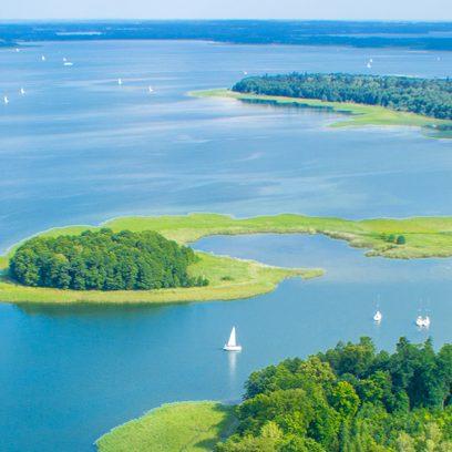 Zdjęcie z lotu ptaka przedstawia jezioro w porze letniej, na którym pływają liczne białe łódki.