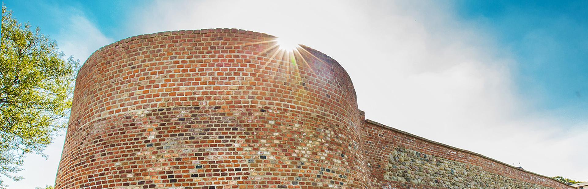 Zdjęcie przedstawia zbliżenie muru przez którego górą przedzierają się promienie słońca.