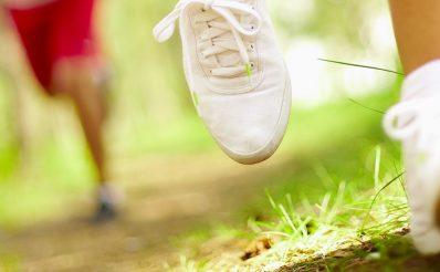 Łydka oraz stopy biegaczki wyposażone w profesjonalne skarpety i buty treningowe. Za biegaczką niewyraźna sylwetka mężczyzny biegnącego leśną drogą.