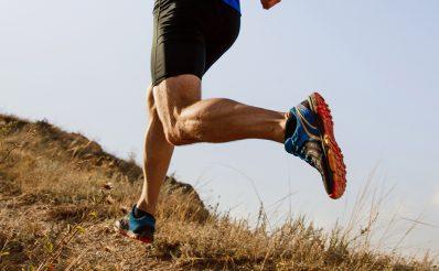 Zawodnik ubrany w profesjonalny strój sportowy, podczas biegu pokonujący wzniesienie. Mężczyzna  odwrócony tyłem do frontu zdjęcia.