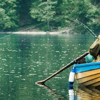 Na zdjęciu widnieje łowiący ryby mężczyzna siedzący na żółto-niebieskiej łódce pośrodku jeziora. Mężczyzna ubrany jest w zgniłozieloną kurtkę i czapkę, a naprężona żyłka wędki wskazuje na to, że zaraz zostania złowiona ryba.