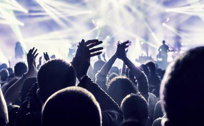 Bardzo mocno oświetlona białymi reflektorami scena muzyczna podczas koncertu zespołu nad głowami bawiącej się i żywo reagującej widowni.