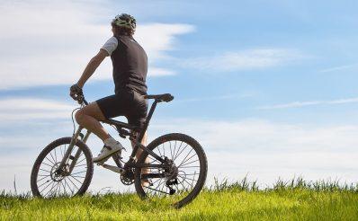 Stojący samotny rowerzysta na mazurskim polu, wśród bujnej zielonej trawy.