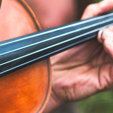 Zdjęcie - ilustracja przedstawiająca skrzypce na których gra artysta.