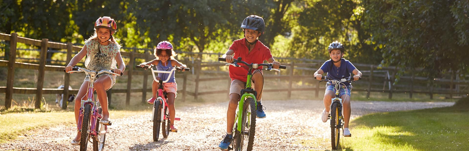 Zdjęcie przedstawia czworo uśmiechniętych dzieci jadących na rowerach żwirową drogą.