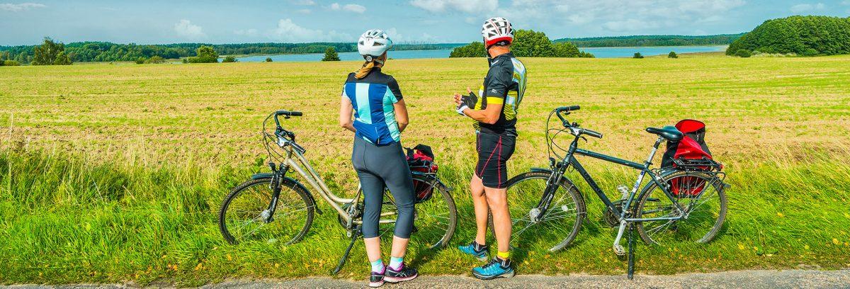 Zdjęcie przedstawia parę rowerzystów podczas postoju na łące, patrzących się w dal gdzie widać niebieskie jezioro.